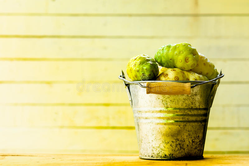 Noni fruit in zinc bucket on table and old wooden background. royalty free stock photos