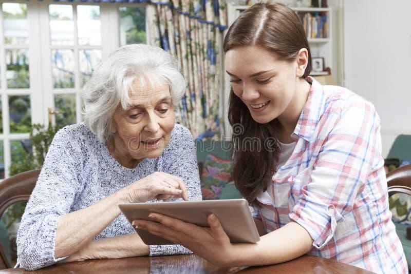 A nonna adolescente della nipote mostrando come usare la linguetta di Digital fotografie stock libere da diritti