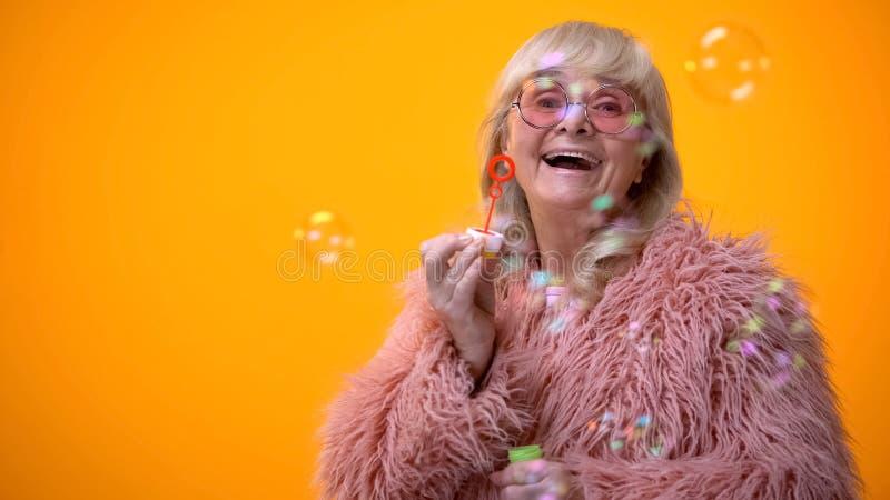 Nonna alla moda divertente in cappotto rosa ed occhiali da sole rotondi che fanno le bolle di sapone, annuncio fotografia stock libera da diritti