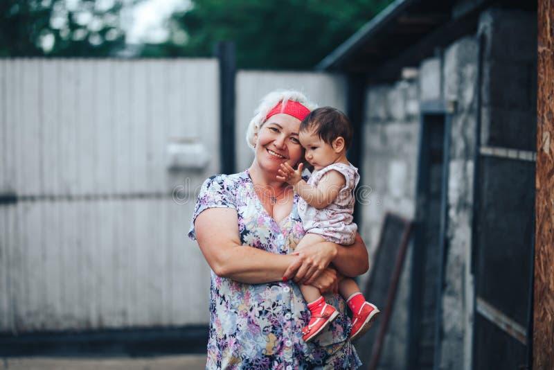 Nonna che abbraccia nipote in natura nel giorno di estate soleggiato fotografia stock libera da diritti