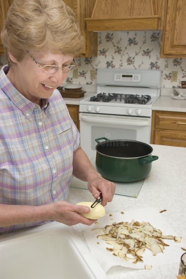 Nonna che cucina nella sua cucina, sbucciante le patate fotografia stock libera da diritti