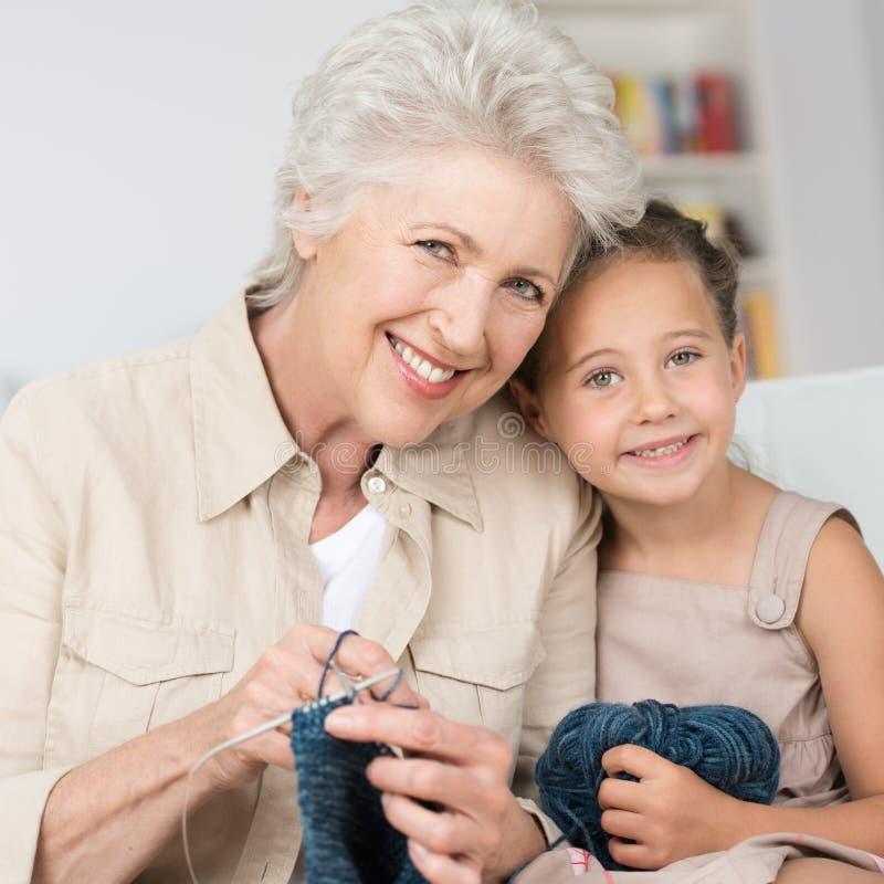 Nonna che insegna alla sua nipote a tricottare fotografia stock