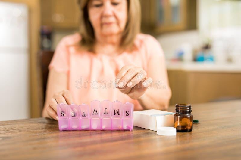 Nonna che mette le compresse su una scatola della pillola immagini stock libere da diritti