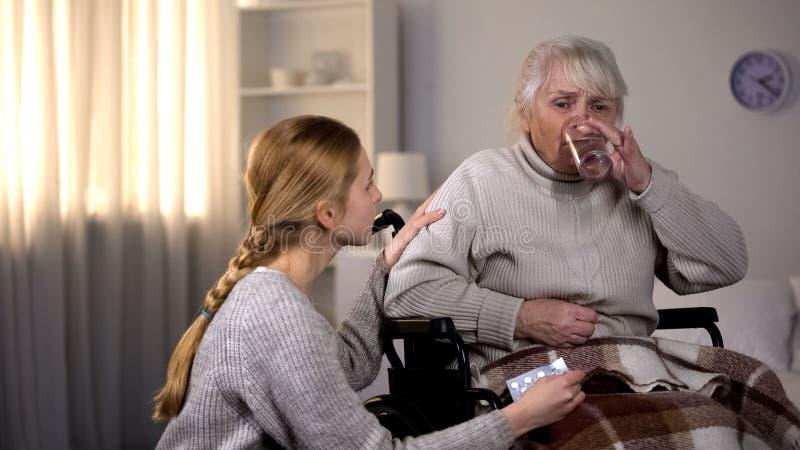 Nonna che prende pillola con acqua, nipote preoccupantesi che sostiene donna malata fotografia stock libera da diritti