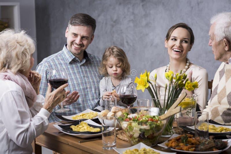 Nonna che propone un pane tostato con la famiglia fotografie stock libere da diritti