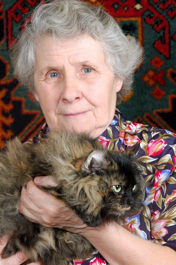 Nonna che si siede con il gatto sulle sue mani immagini stock