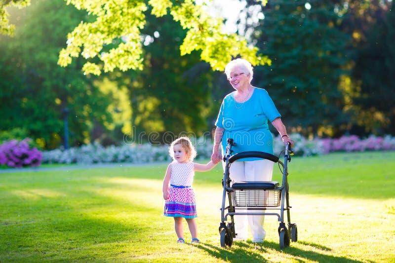 Nonna con il camminatore e la bambina in un parco fotografia stock libera da diritti