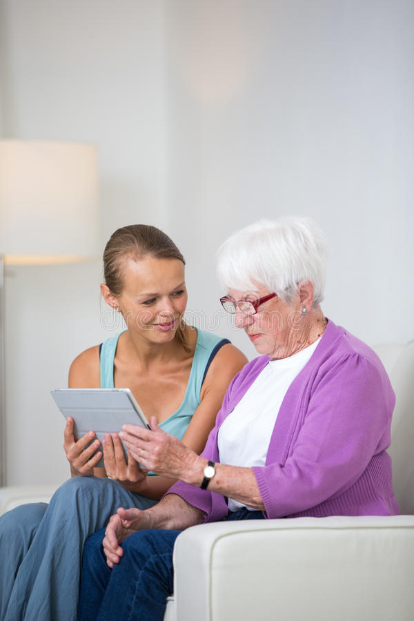 Nonna con la sua gran-figlia che si siede su un sofà fotografia stock