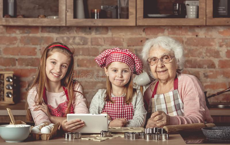 Nonna con le nipoti che cercano una ricetta in compressa fotografia stock libera da diritti