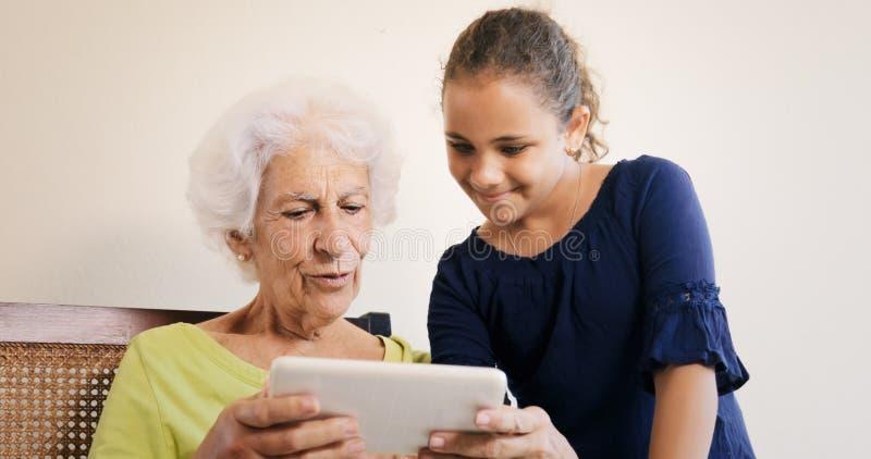 Nonna d'istruzione della bambina come utilizzare compressa per Internet immagine stock