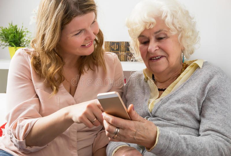 Nonna d'istruzione della nipote come utilizzare smartphone immagine stock libera da diritti