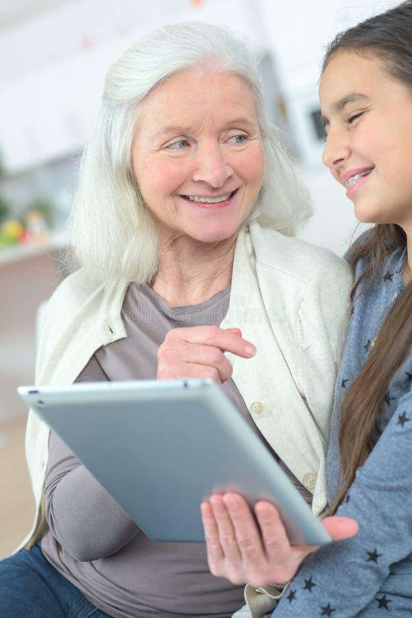Nonna d'istruzione della ragazza come utilizzare compressa fotografie stock