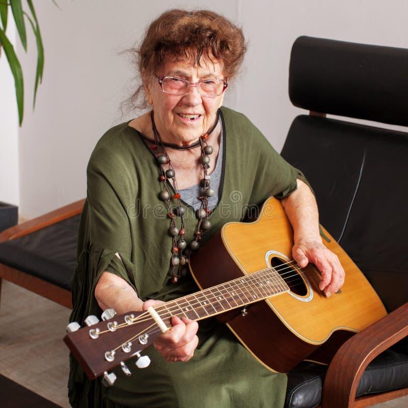 Nonna di 90 anni per giocare la chitarra fotografie stock