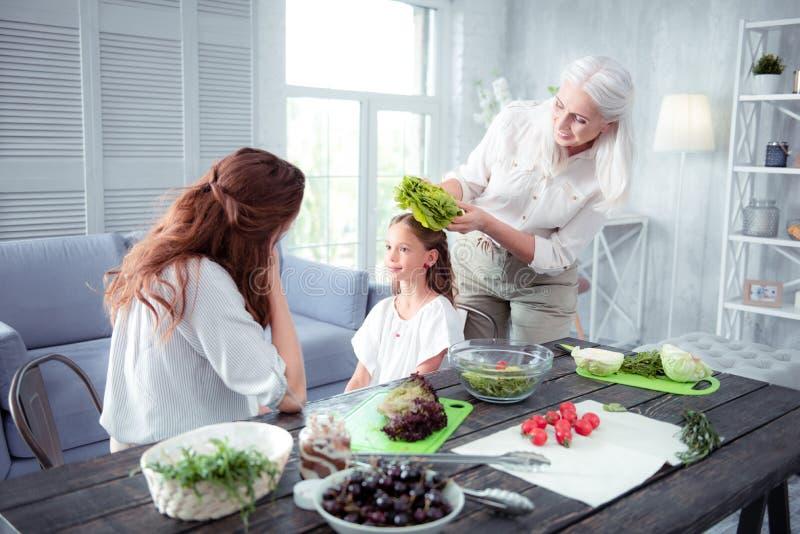 Nonna divertente divertendosi mentre mettendo una certa lattuga sulla testa della ragazza fotografie stock libere da diritti