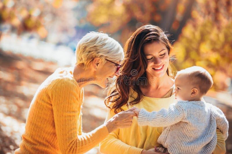 Nonna e madre che sorridono al bambino nel parco di autunno immagine stock
