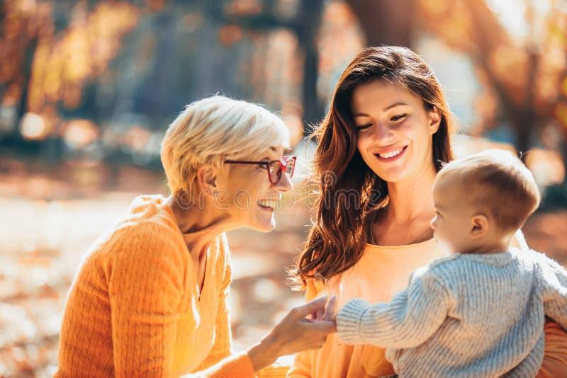 Nonna e madre che sorridono al bambino nel parco di autunno fotografia stock libera da diritti