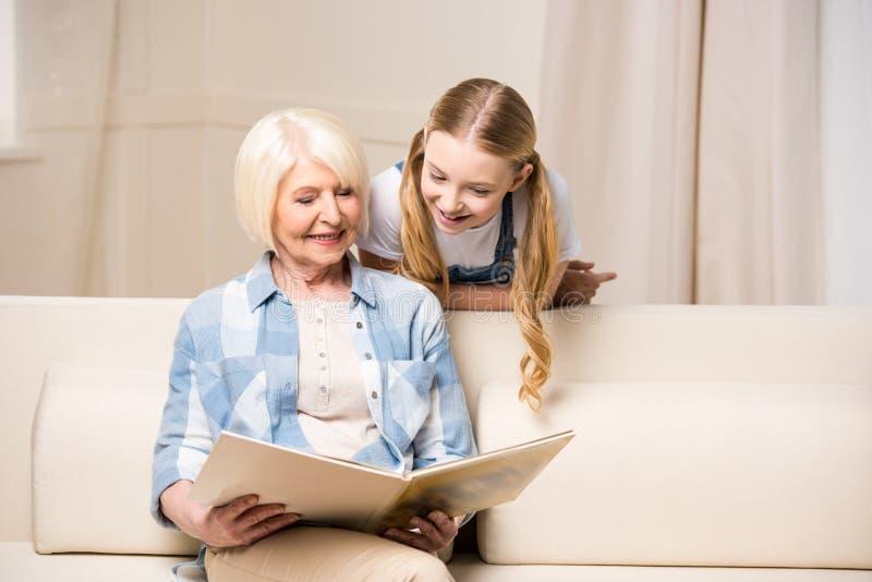 Nonna e nipote che esaminano album di foto a casa fotografie stock
