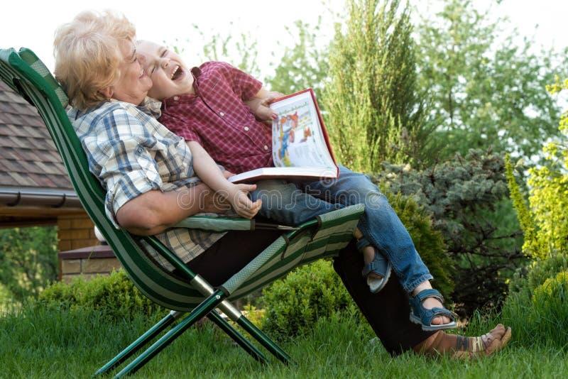 Nonna e nipote che leggono un libro all'aperto Storie divertenti immagine stock