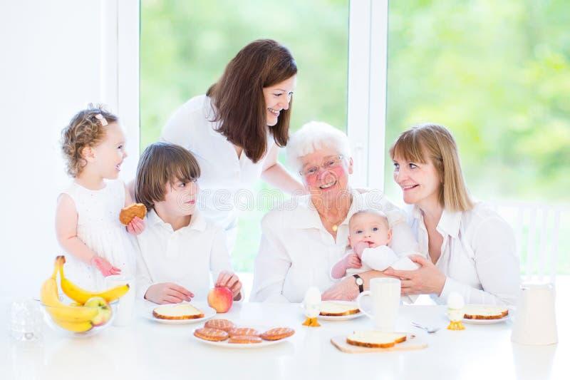 Nonna felice che gode della prima colazione con la sua famiglia immagine stock