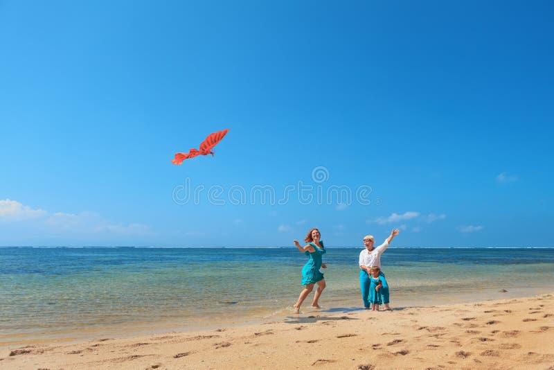 Nonna, madre e aquilone di lancio del bambino sulla spiaggia del mare fotografia stock