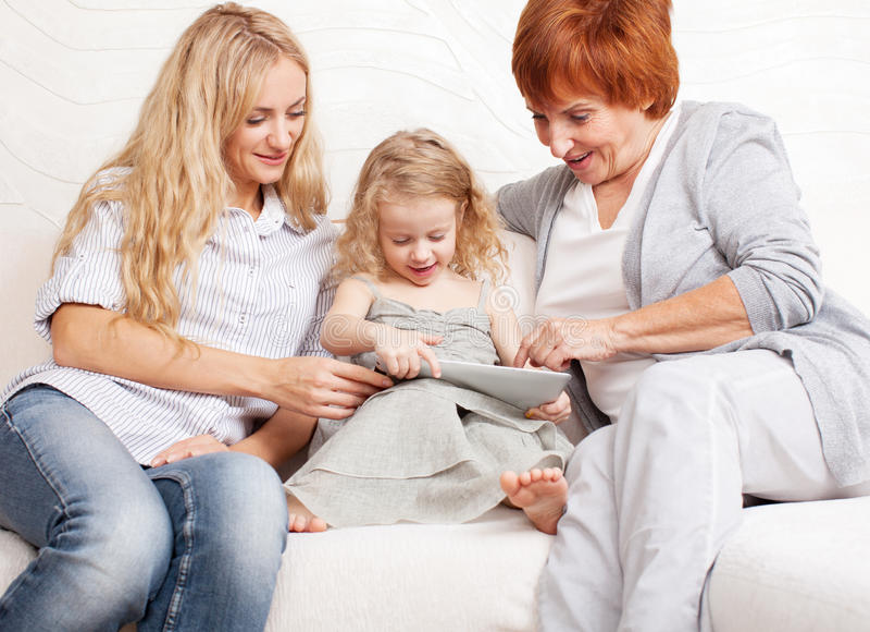Nonna, madre e bambina a casa sul sofà. fotografia stock