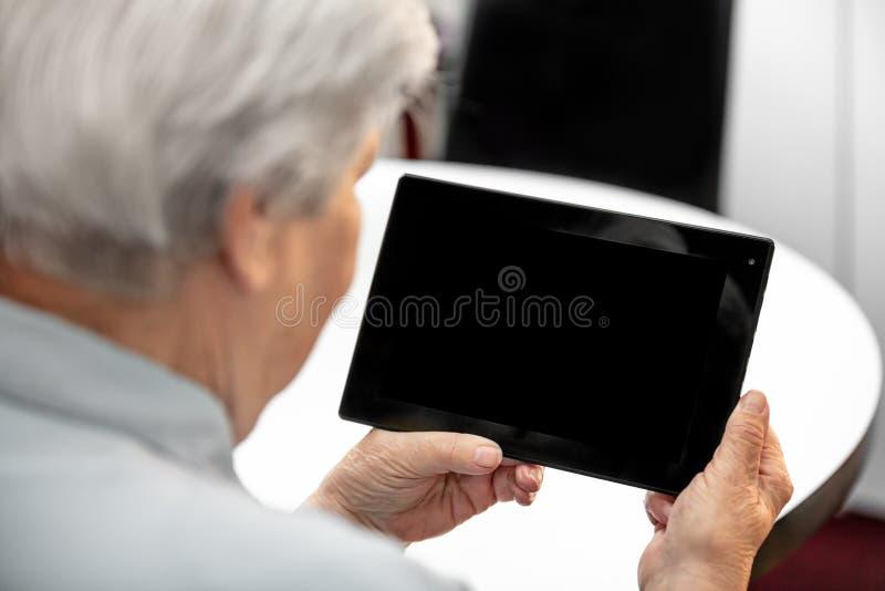 Nonna moderna che esamina lo scrittorio da una compressa, donne anziane fotografie stock libere da diritti