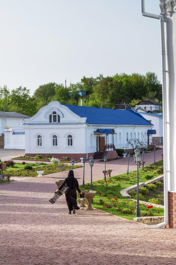 Nonne chrétienne orthodoxe qui va avec des outils de jardin par la cour intérieure du couvent photos libres de droits