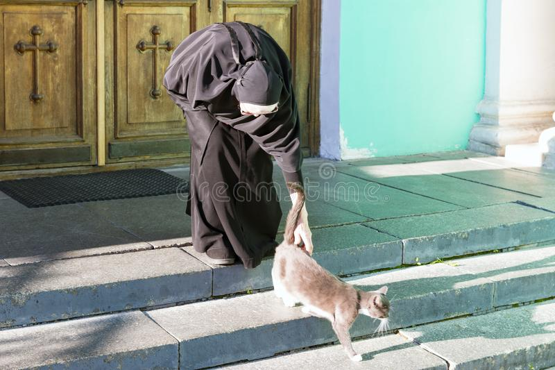 Nonne, die eine Katze streichelt lizenzfreie stockfotografie