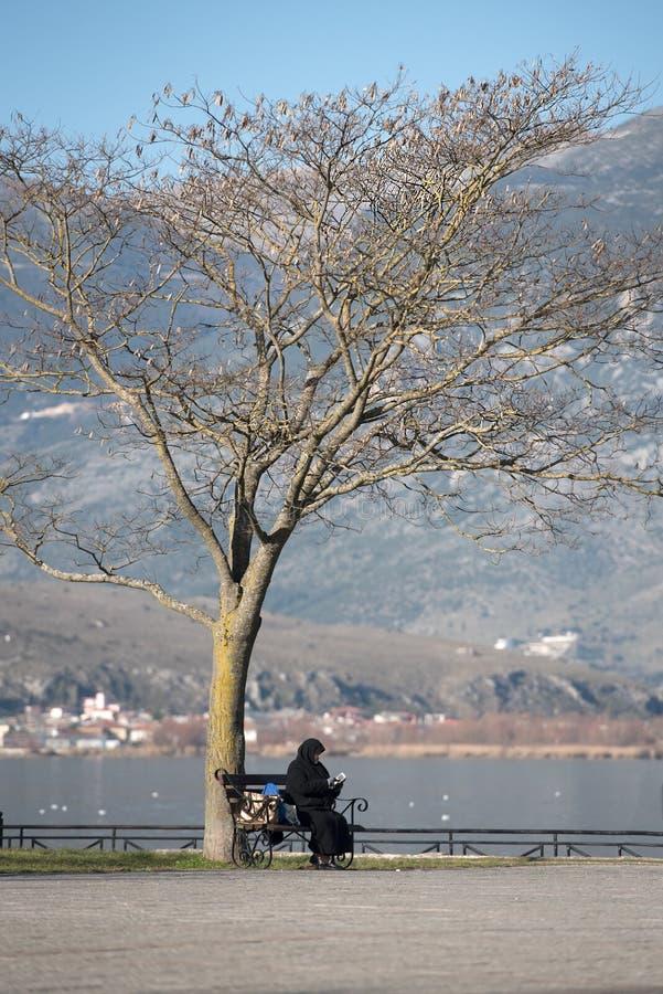 Nonne orthodoxe avec le téléphone se reposant sur le banc sous un grand arbre par image libre de droits