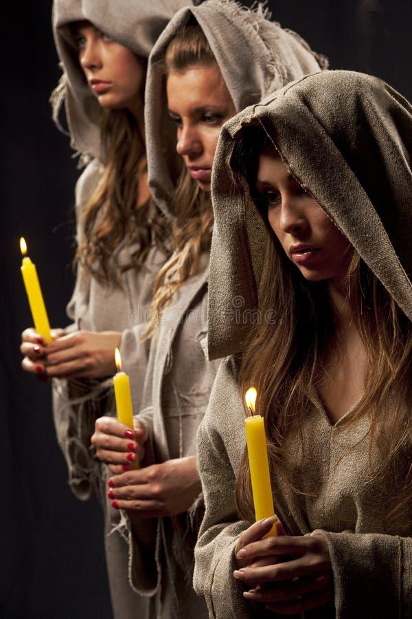 Nonnes praing avec des bougies photographie stock libre de droits