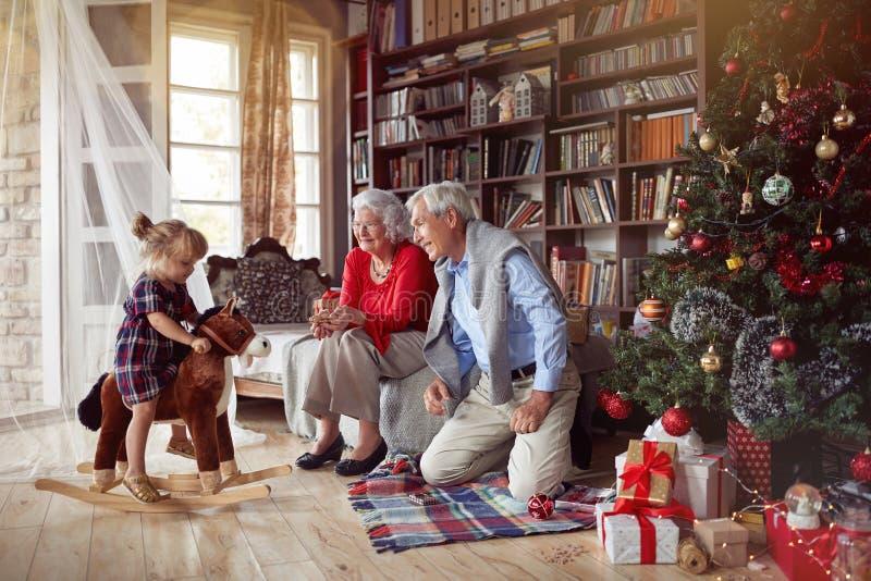 Nonni allegri e bambina che giocano insieme per il Natale fotografia stock libera da diritti