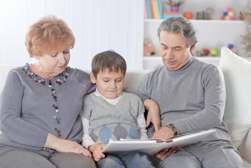 Nonni amorosi con il nipote che si siede sul sof? immagini stock