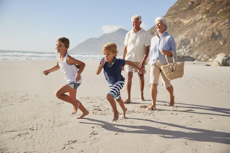 Nonni che corrono lungo la spiaggia con i nipoti immagini stock libere da diritti