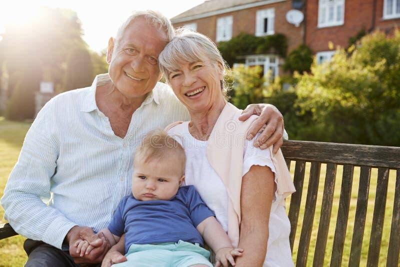 Nonni che si siedono su Seat in giardino con il nipote del bambino fotografia stock libera da diritti