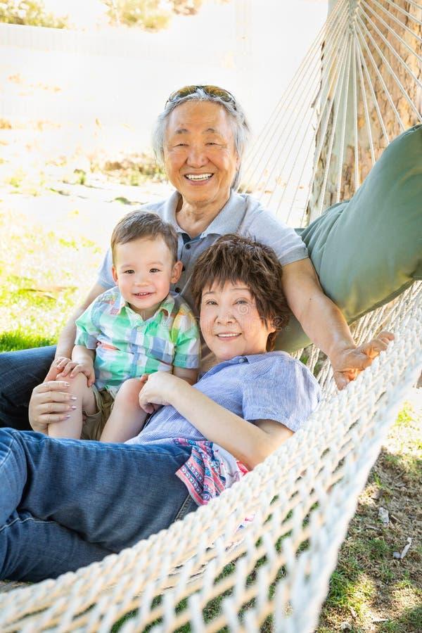 Nonni cinesi in amaca con il bambino della corsa mista immagini stock