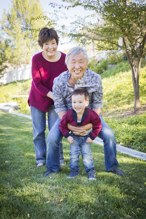Nonni cinesi divertendosi con il loro nipote O della corsa mista immagini stock libere da diritti