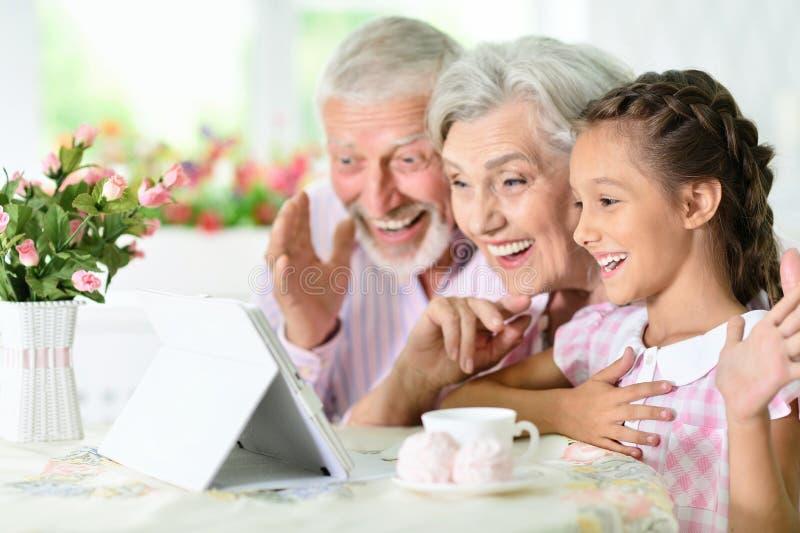 Nonni con la sua nipote che per mezzo della compressa immagine stock