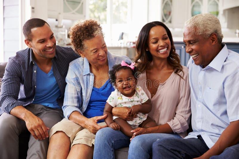 Nonni e genitori con una neonata sul ginocchio del ½ s del ¿ del mumï immagini stock