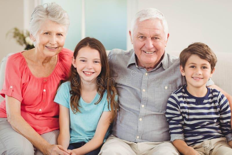 Nonni e nipoti che si siedono insieme sul sofà fotografia stock libera da diritti