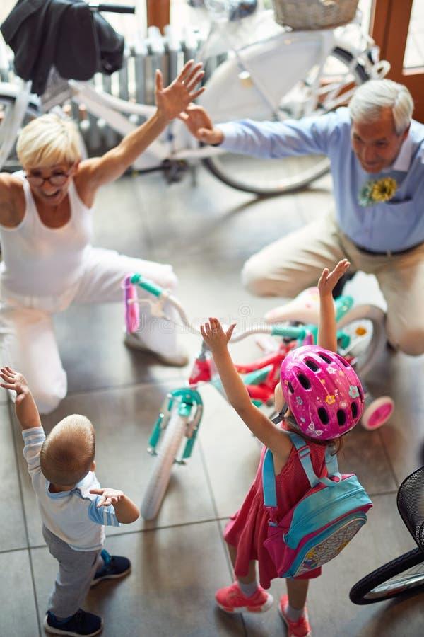 Nonni felici con i nipoti che comprano nuova bicicletta fotografia stock libera da diritti