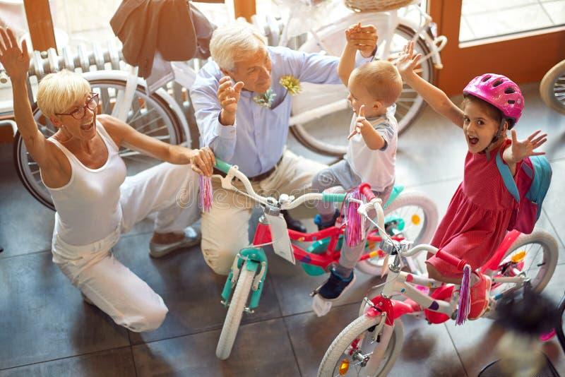 Nonni felici con i nipoti che comprano nuova bicicletta vista superiore immagine stock libera da diritti