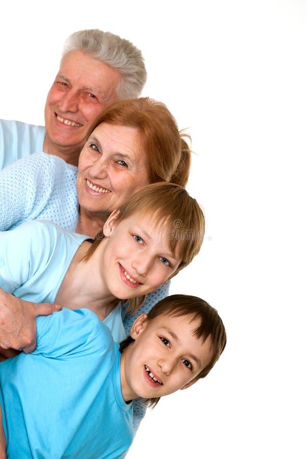 Nonni felici di misericordia con i nipoti imbrogliati immagini stock libere da diritti