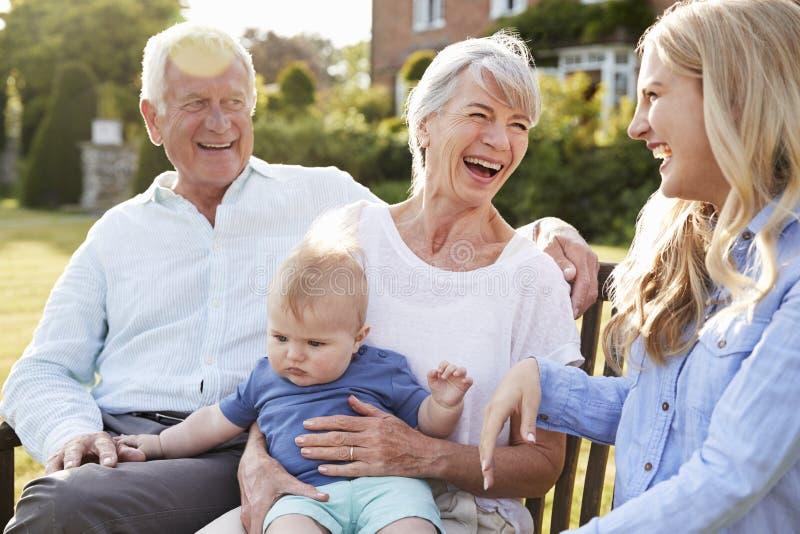 Nonni Sit Outdoors With Baby Grandson e figlia dell'adulto fotografia stock libera da diritti
