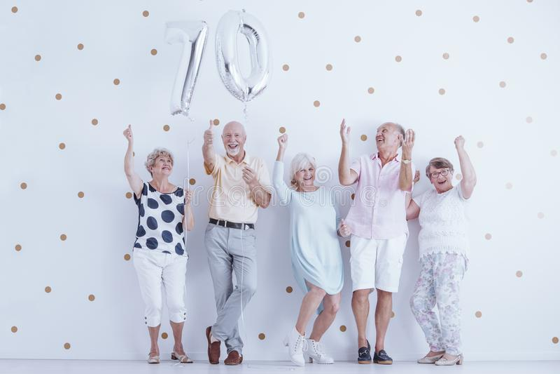Nonni sorridenti che godono del compleanno del ` s dell'amico immagine stock