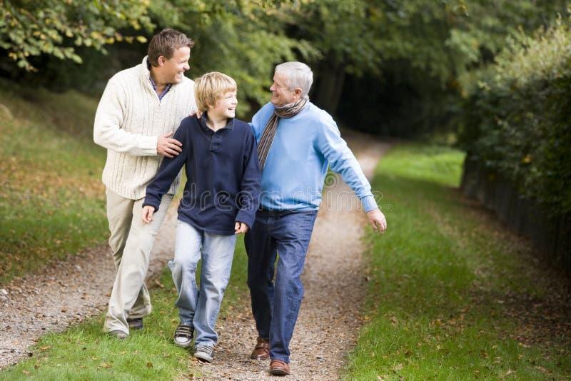 Nonno che cammina con il figlio ed il nipote fotografia stock libera da diritti