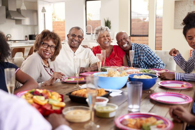 Nonno che fa una condizione alla tavola di cena che celebra con la sua famiglia, fine del pane tostato su immagine stock libera da diritti