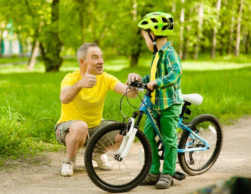 Nonno che parla con il suo nipote che guida una bicicletta immagine stock