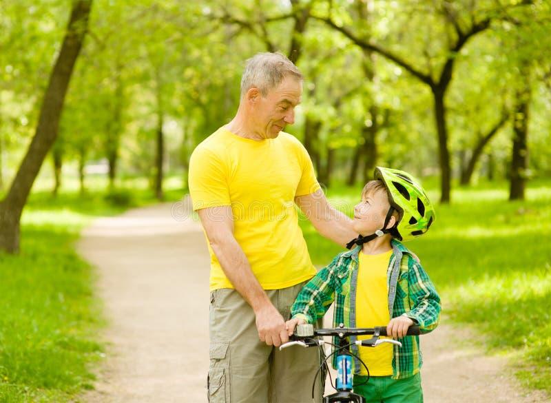 Nonno che parla con il suo nipote che guida una bicicletta fotografia stock