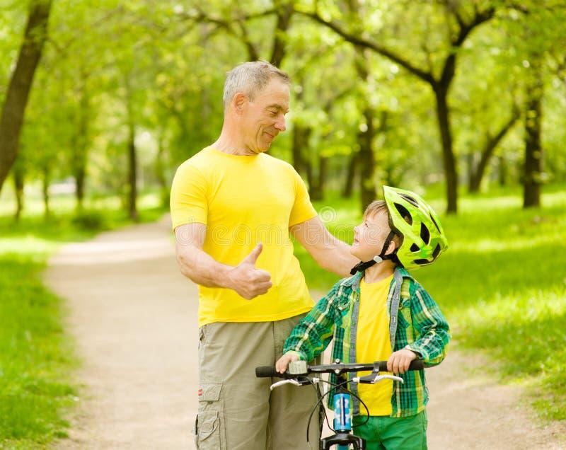 Nonno che parla con il suo nipote che guida una bicicletta e che mostra i pollici su fotografia stock