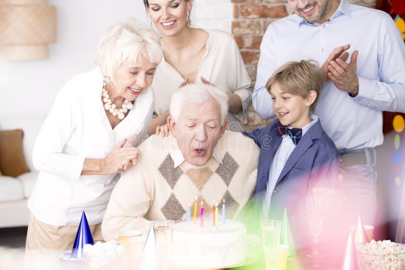 Nonno che spegne le candele sulla torta di compleanno immagine stock